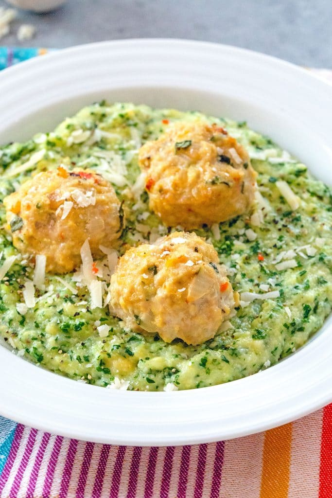 three chicken meatballs on kale polenta in a white bowl.