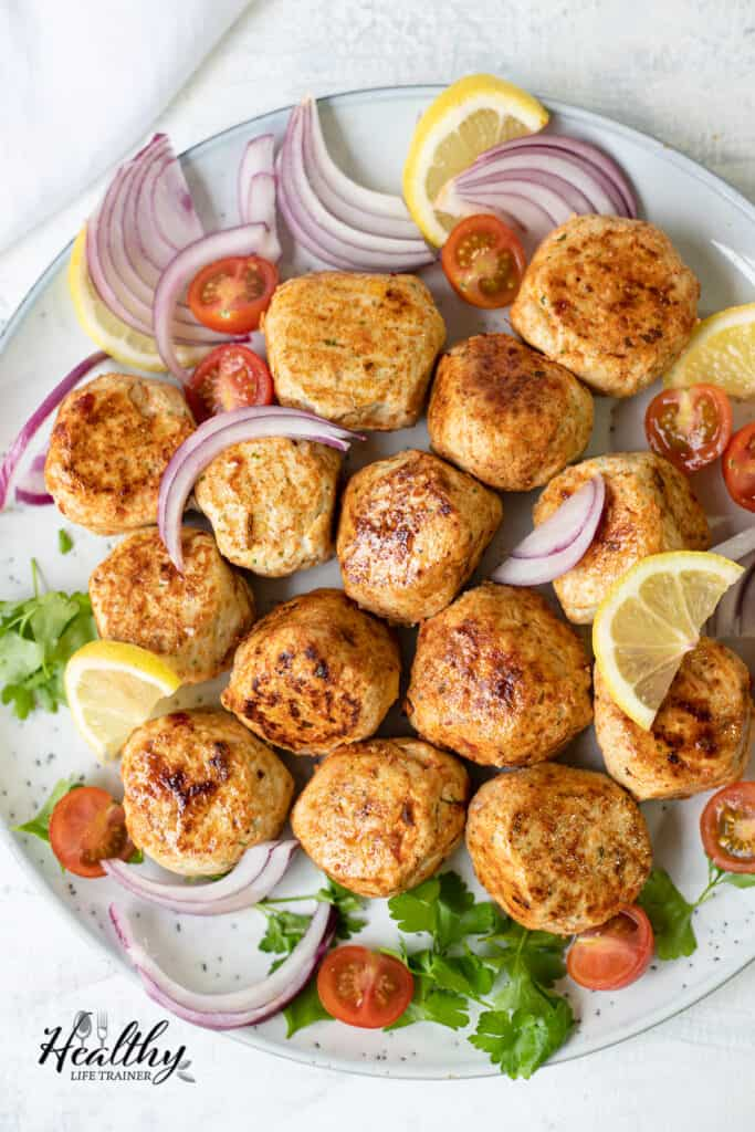 overhead shot of the chicken kofta with onions, lemons, and tomatoes.