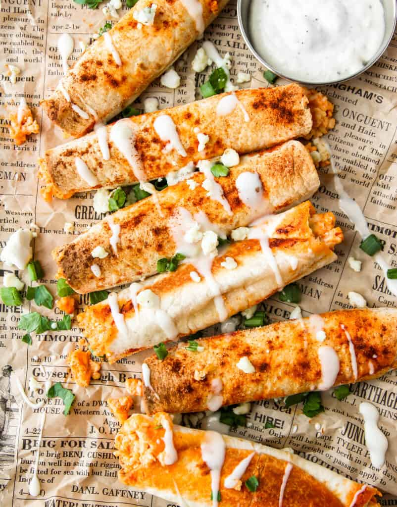 overhead shot of buffalo chicken taquitos with ranch drizzled and crumbled blue cheese, scallions, and parsley on brown newsprint paper.