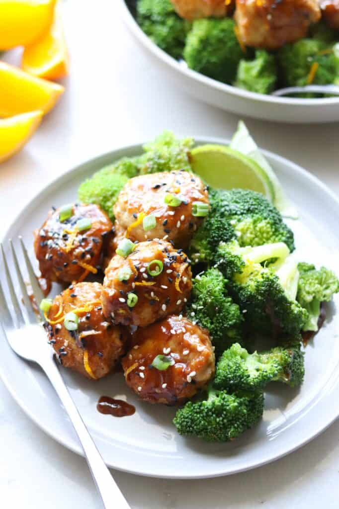 orange chicken meatballs with a fork, broccoli and lime wedge.