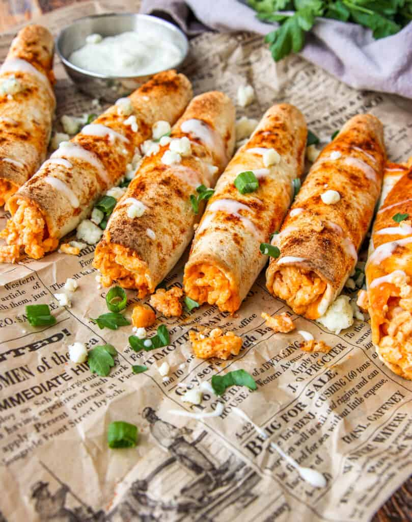 angled shot of buffalo chicken taquitos with ranch drizzled and crumbled blue cheese, scallions, and parsley on brown newsprint paper.