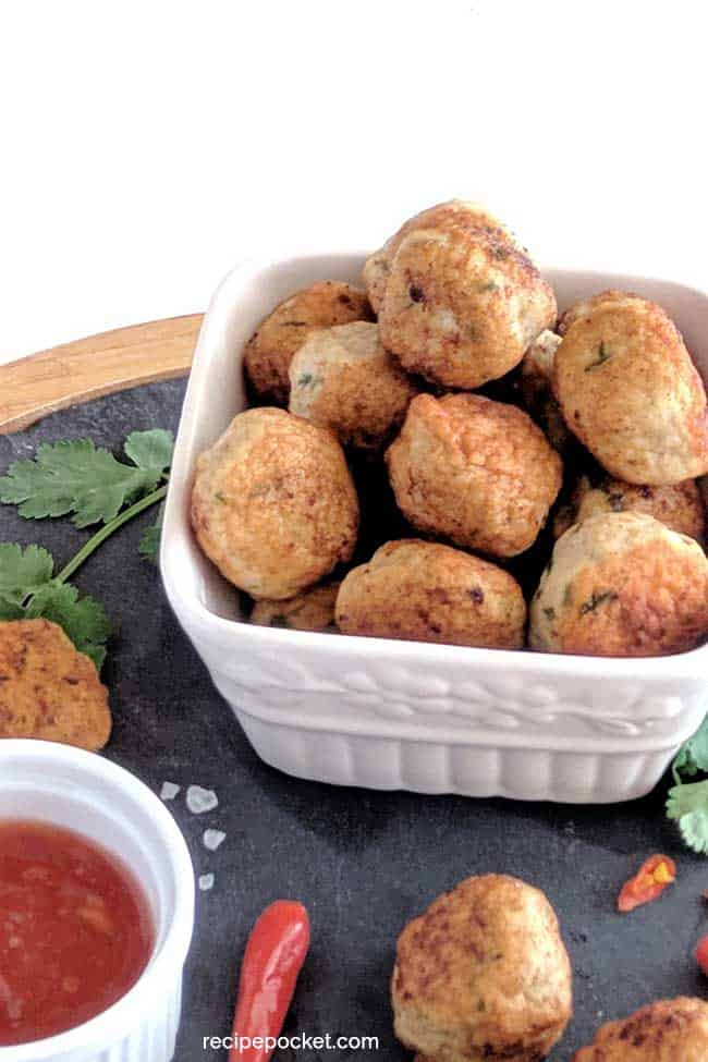 chicken meatballs in a white container with a sweet chili sauce.