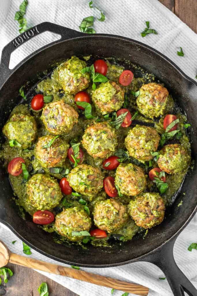 chicken pesto meatballs with grape tomatoes in a cast iron skillet.