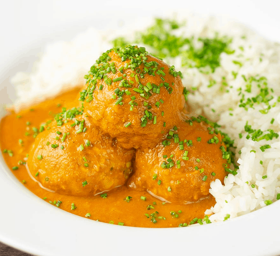 a pile of the chicken kofta masala topped with chives and rice in the background.