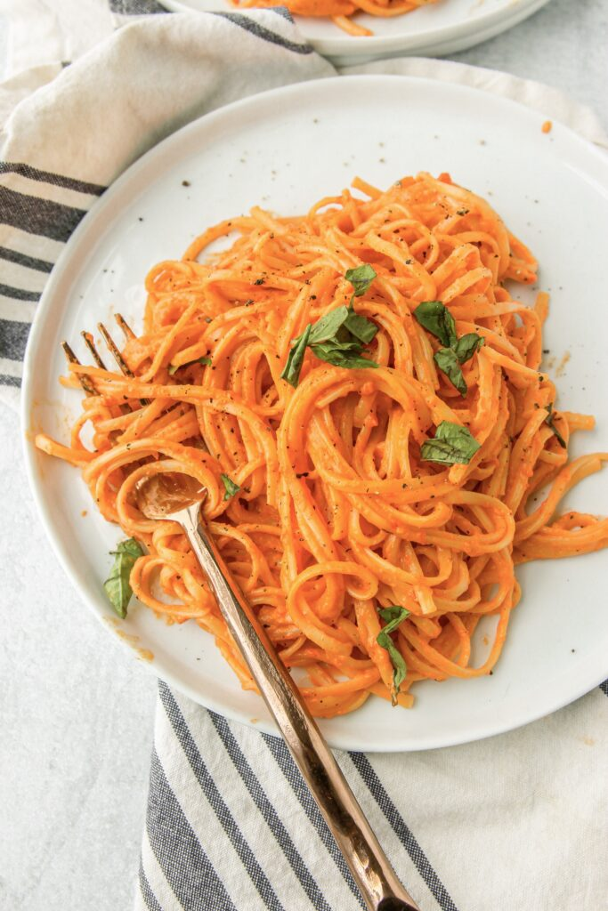 overhead shot of the creamy roasted red pepper sauce over linguini on a small white plate with a copper fork. One a blue and white stripped napkin.