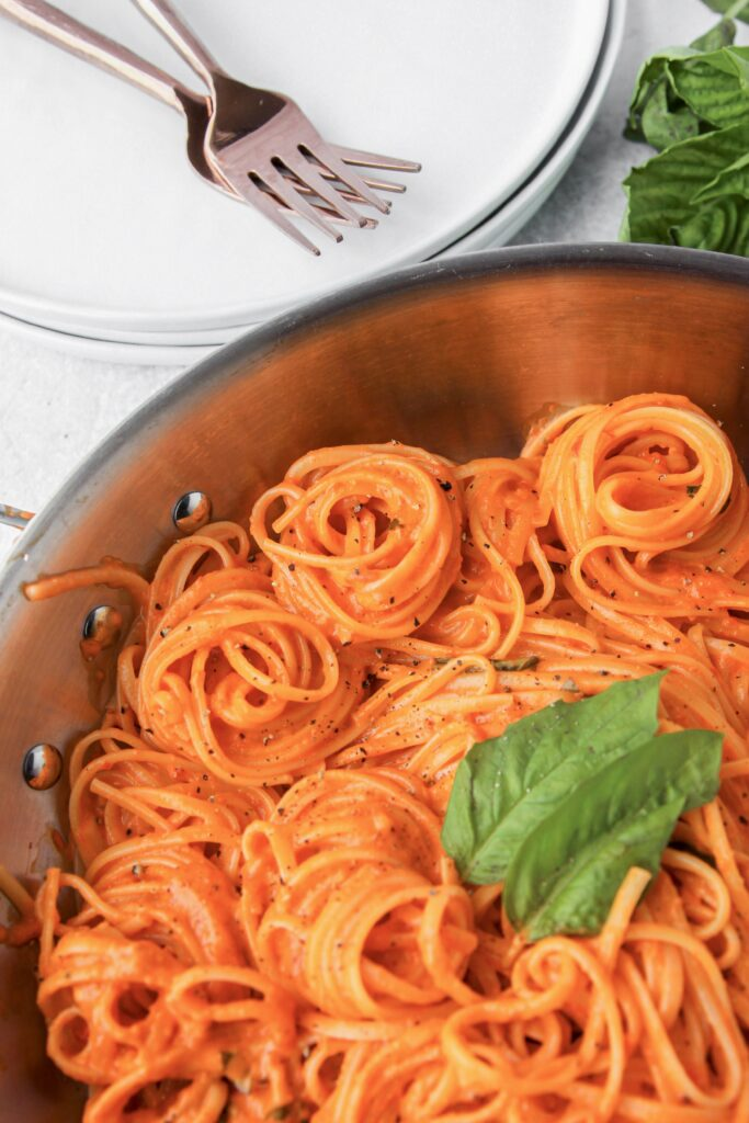 overhead shot of spiraled linguine in the creamy roasted red pepper sauce in a stainless steel pan. Forks and plates off to the side.