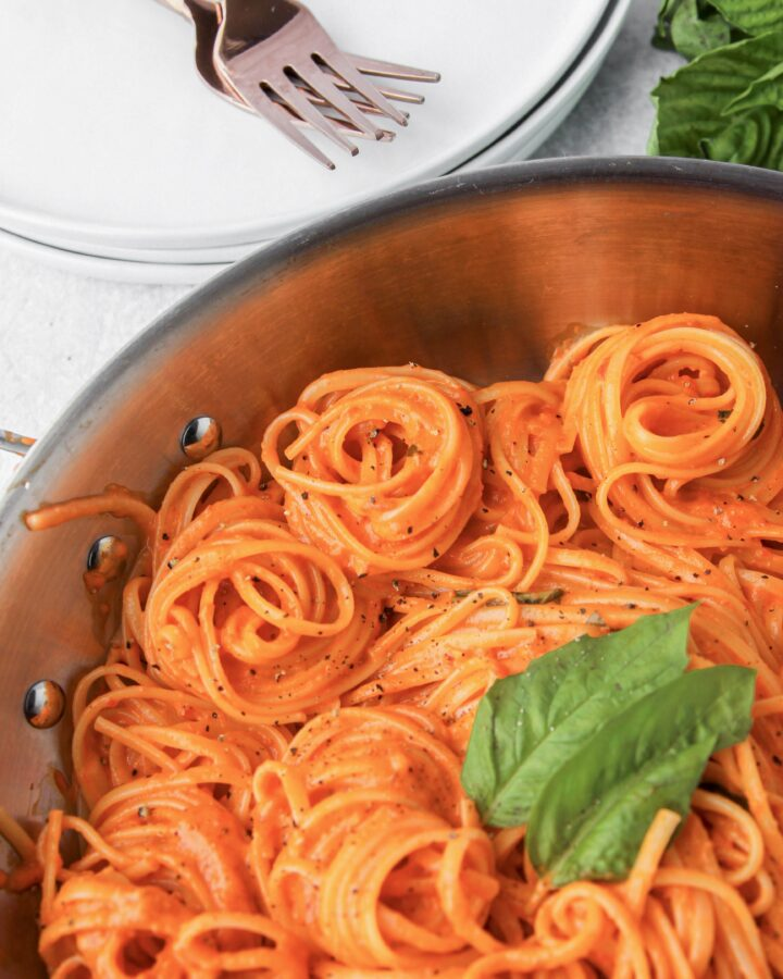 spiraled linguini in a creamy roasted red pepper sauce with white places and 2 copper forks