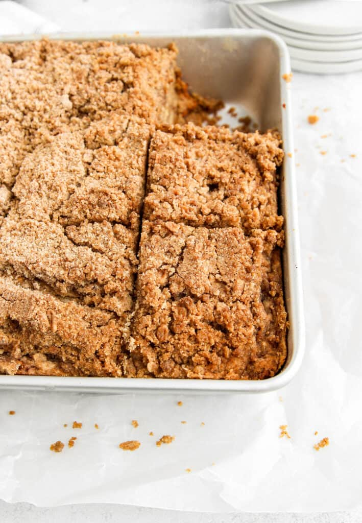 the coffee cake in the silver 8x8 baking pan, crumbs scattered about, plates in the background.