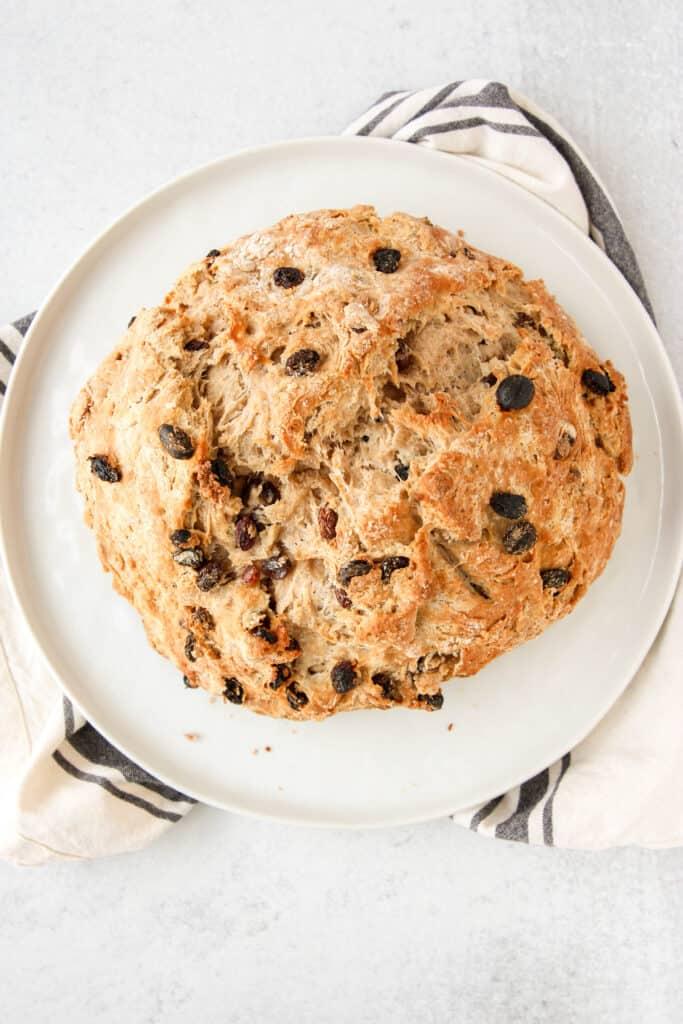 overhead shot of the cinnamon raisin soda bread on a white round plate.