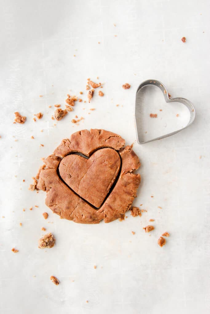 edible cookie dough with the heart shape and the cookie cutter to the side.