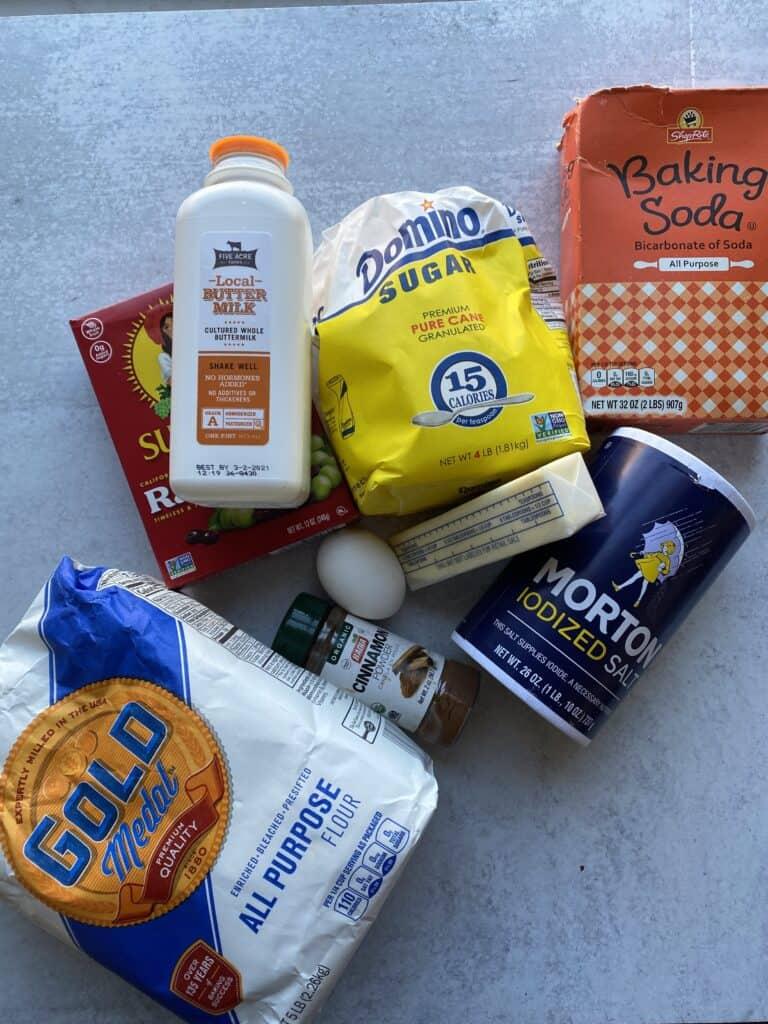 overhead shot of ingredients. Buttermilk, raisins, flour, cinnamon, an egg, butter, sugar, baking soda, salt.