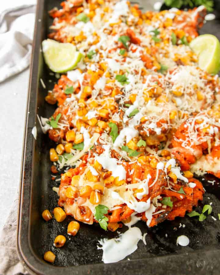 the Mexican street corn waffle fries on a baking tray with parsley in the back.