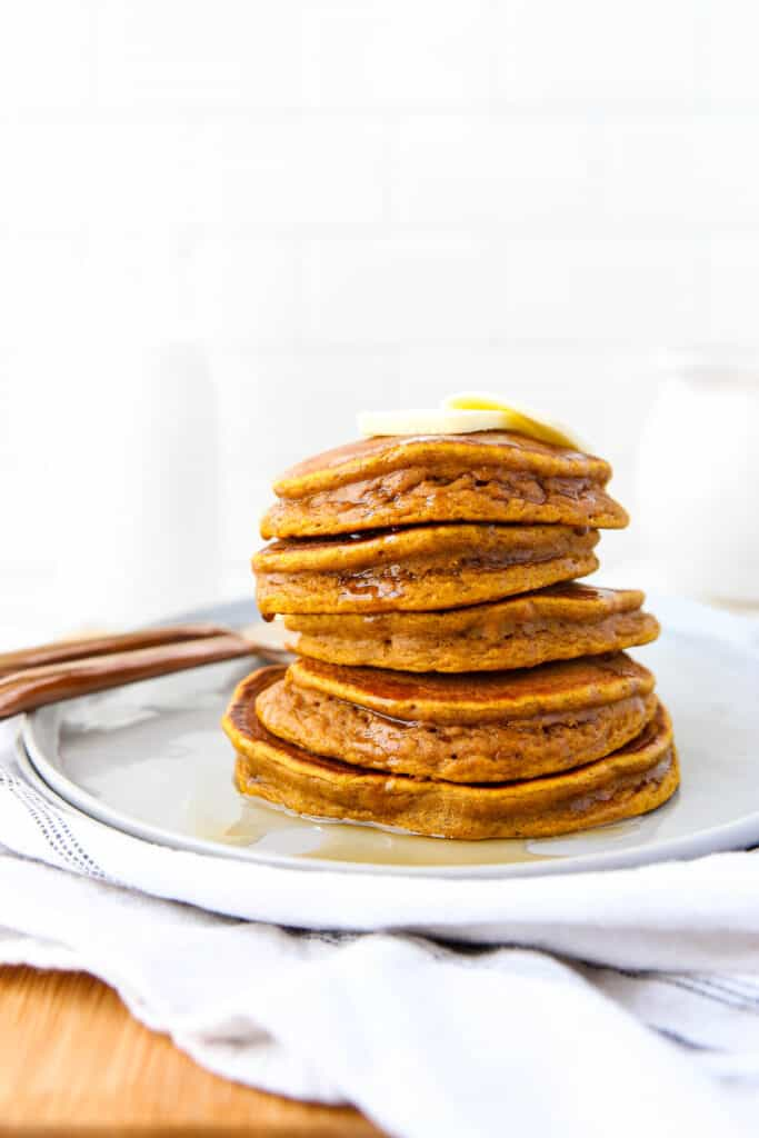 stack of 5 pumpkin pancakes with butter on top.