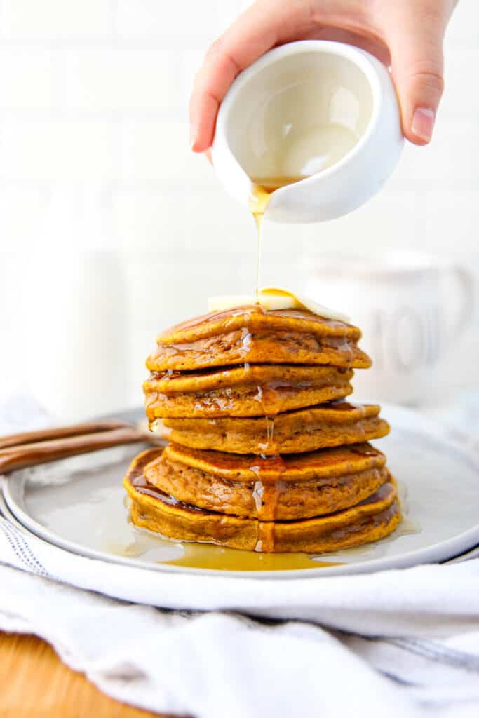 stack of 5 pumpkin pancakes on a grey round plate with maple syrup being drizzled overtop.