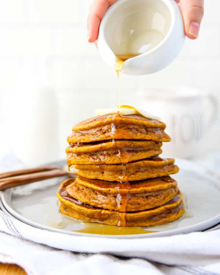 stack of 5 pumpkin pancakes with syrup drizzle.