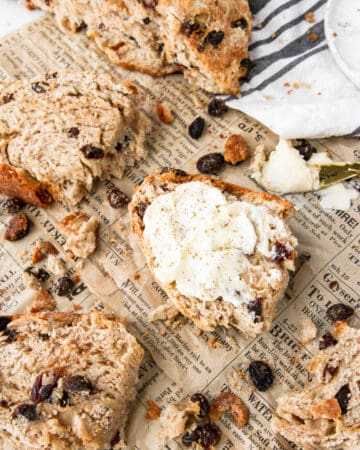 overhead shot of a slice of cinnamon raisin soda bread with butter on brown newsprint paper