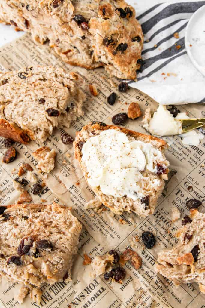 overhead shot of a slice of cinnamon raisin soda bread with butter on brown newsprint paper with raisins and crumbs