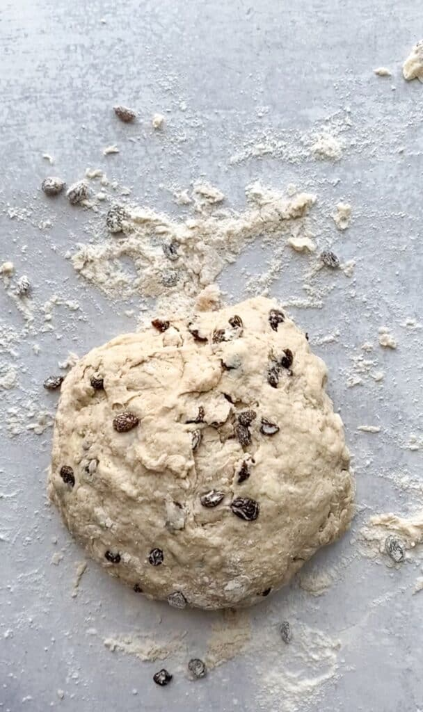 overhead shot of the unbaked dough on a grey cement surface with flour and raisins scattered about.