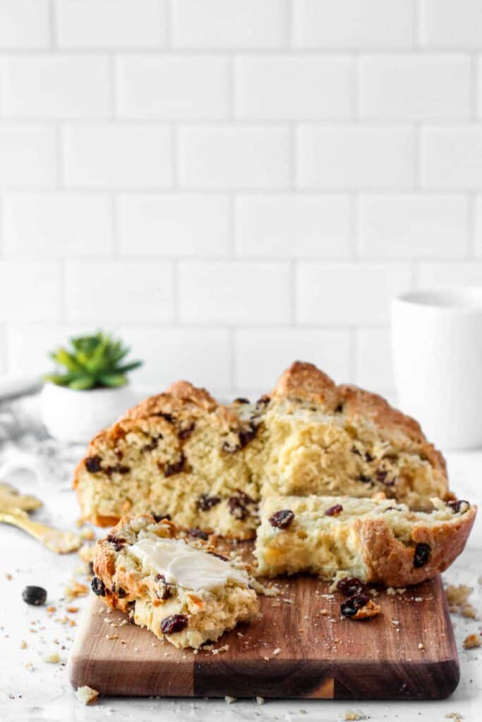 sliced Irish soda bread on a wood cutting board. White tile background with a white mug and green succulent.