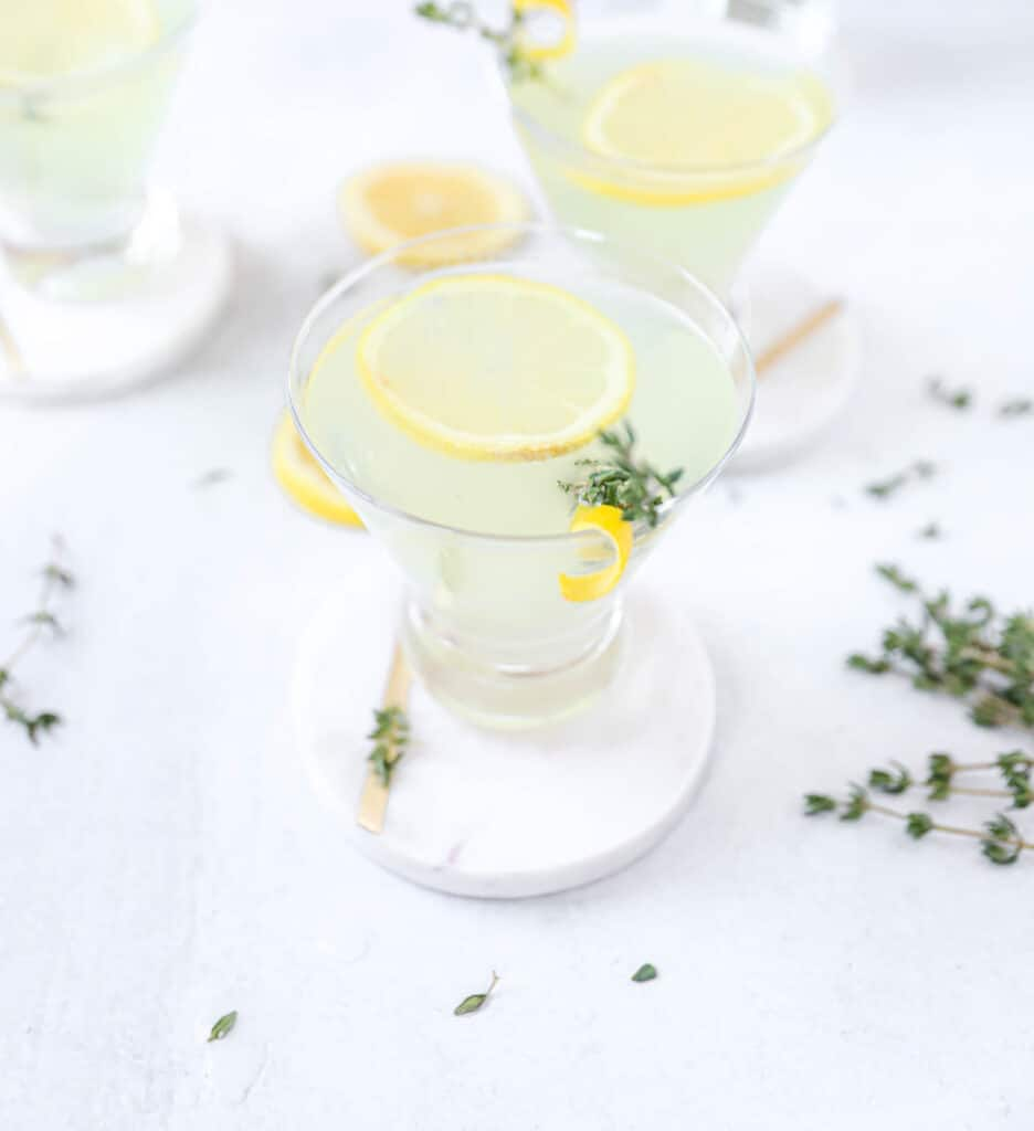 limoncello martini on a white coaster, with two martinis in the background and fresh thyme scattered.