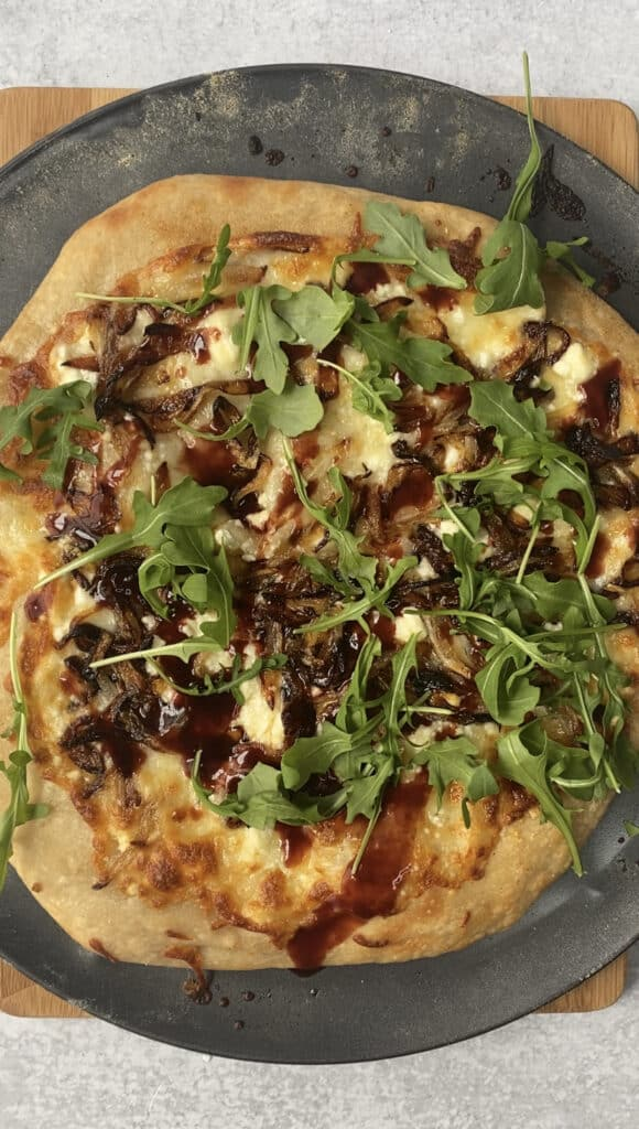 overhead shot of the finished pizza topped with the arugula and the raspberry balsamic vinegar.