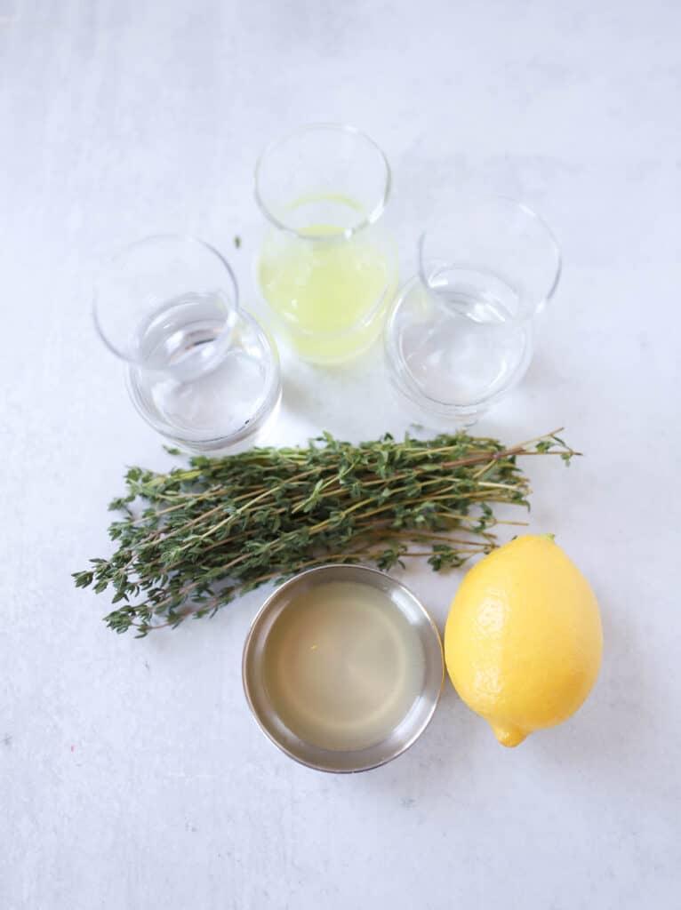 overhead shot of the limoncello martini ingredients: vodka, triple sec, limoncello, thyme, lemon juice, a lemon