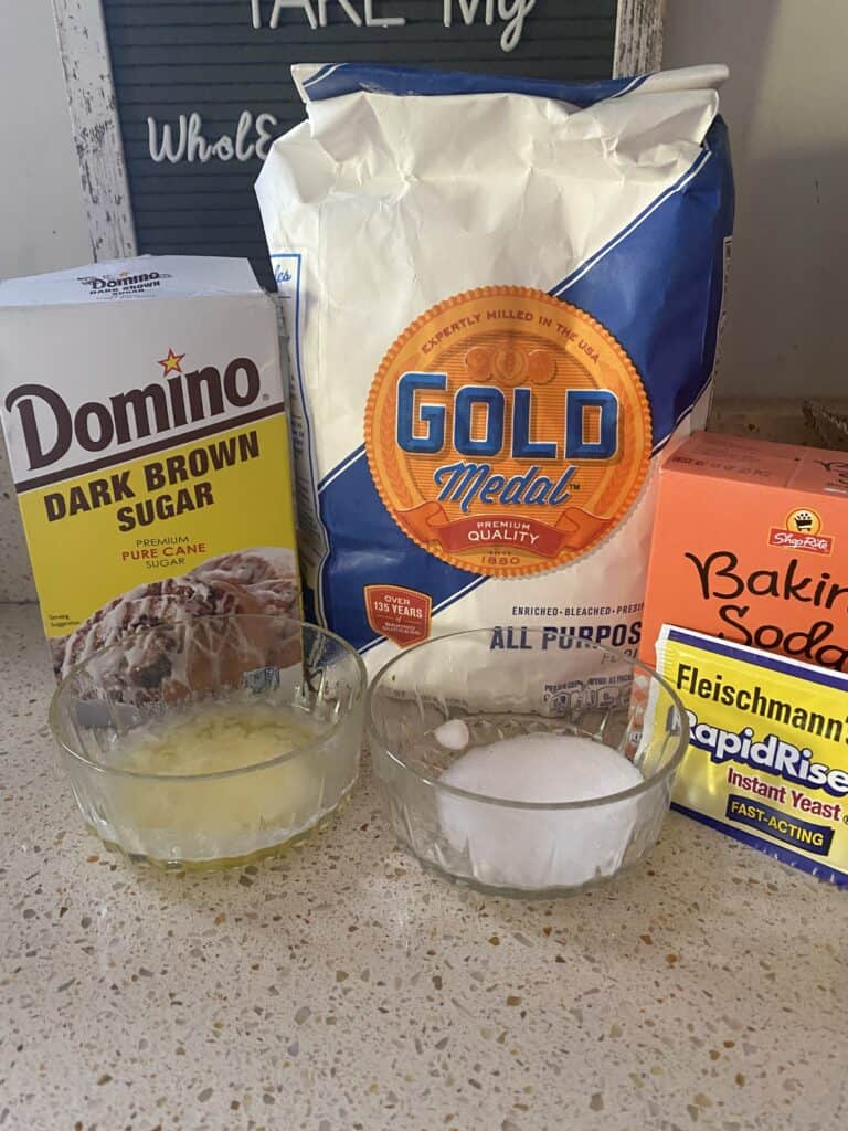 photo showing the ingredients on the counter: box of brown sugar,  melted butter, salt, bag of flour, box of baking soda, packet of rapid rise yeast.