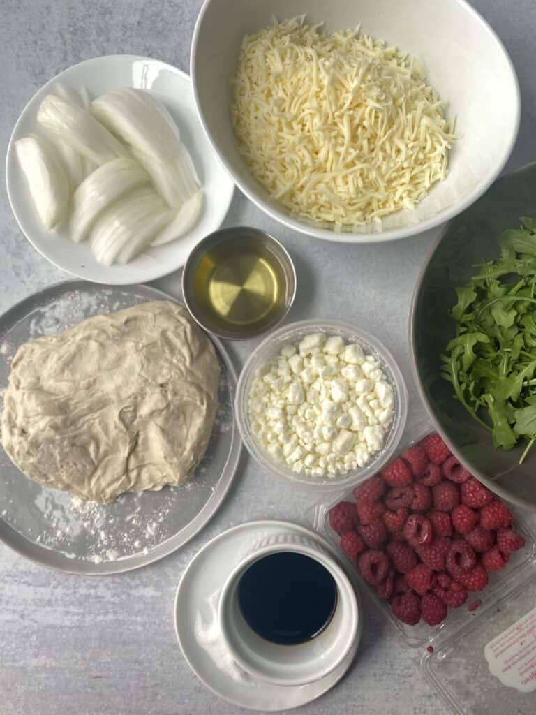 overhead shot of the pizza ingredients: slice white onions, Mozzarella cheese, olive oil, goat cheese, pizza dough, arugula, raspberries, sugar, and balsamic vinegar.