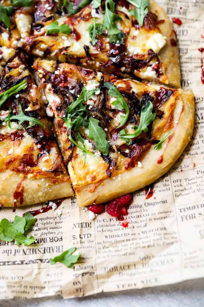 close shot of the goat cheese and onion pizza with raspberry balsamic on brown newsprint paper.