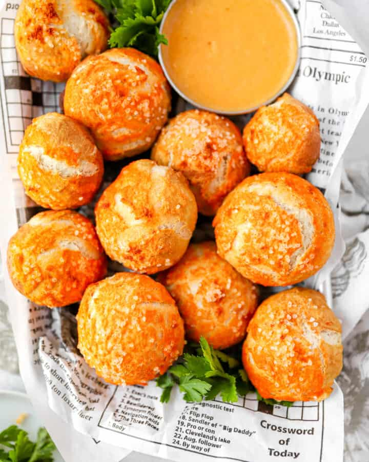 overhead shot of the spicy pretzel bites on newsprint food paper with a beer cheese and parsley.