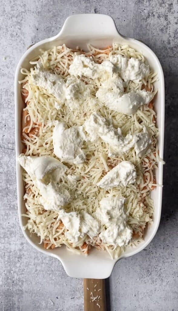 overhead shot of the penne vodka bake in the casserole dish now topped with the Mozzarella and Burrata.