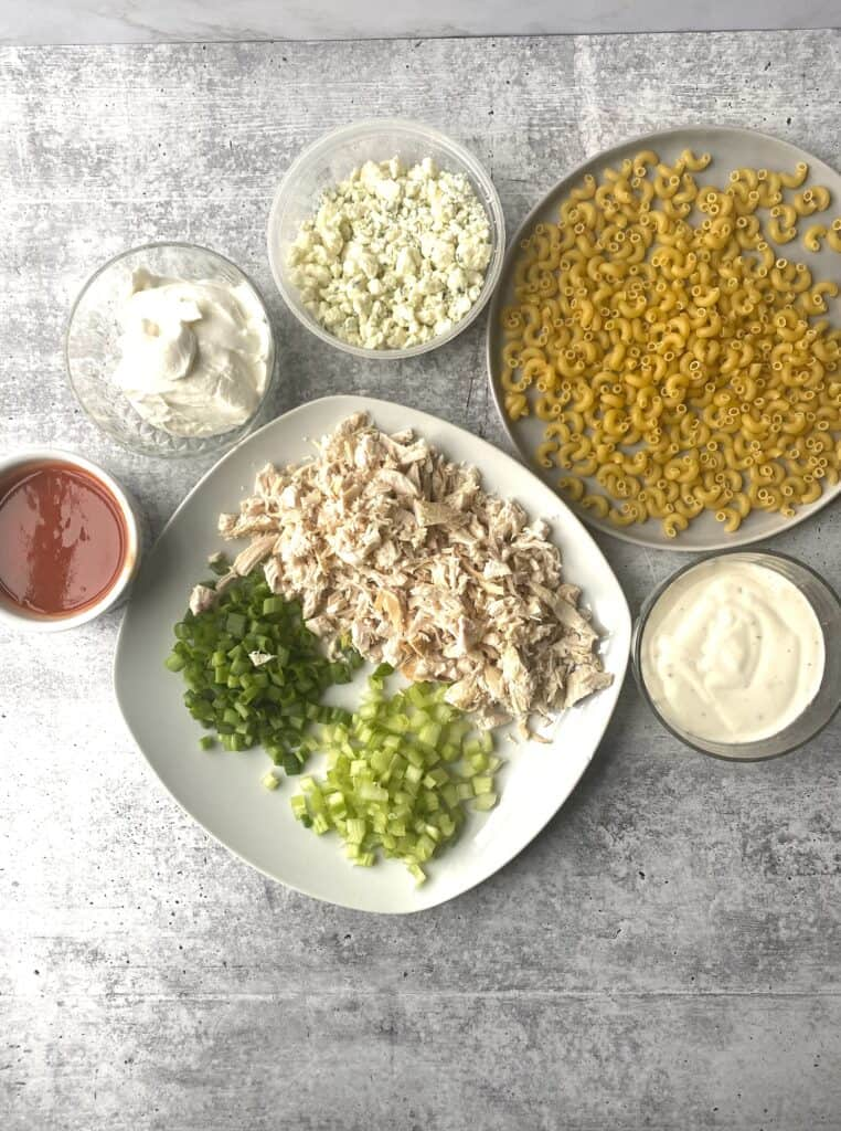 overhead shot of the ingredients. Blue cheese crumbles, noodles, sour cream, hot sauce, ranch dressing, scallions, celery, rotisserie chicken.