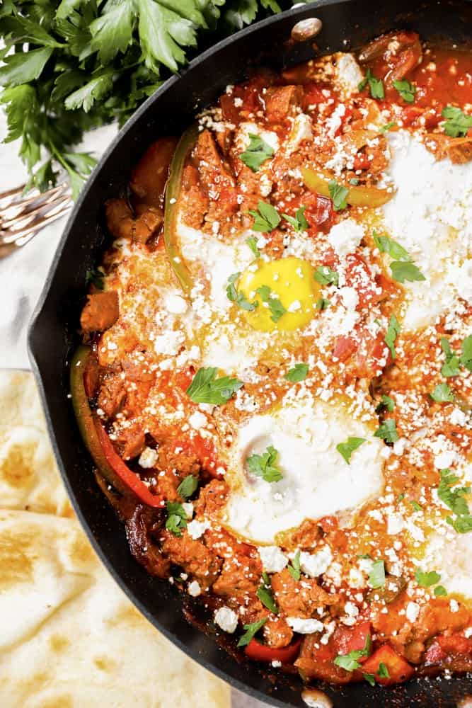 overhead shot of the shakshuka with naan off to the side.