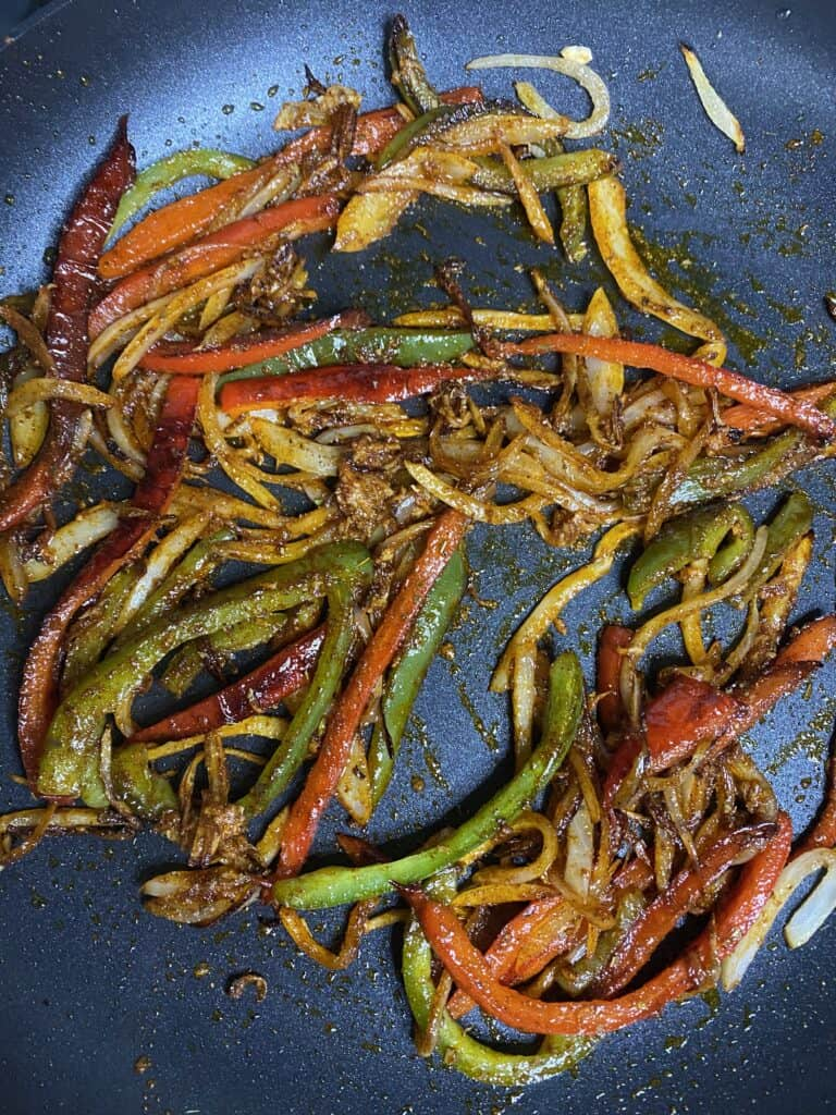 the peppers and onions in the pan coated with the spice mix.