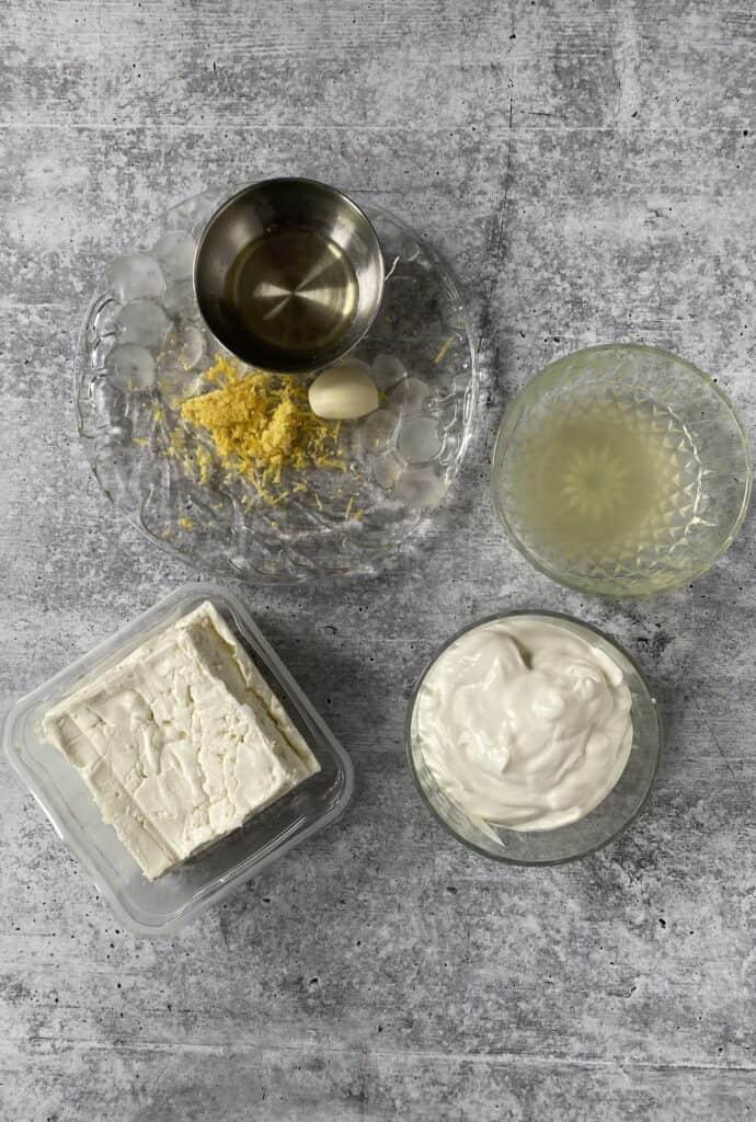 overhead shot of the ingredients: feta cheese, lemon zest, lemon juice, garlic clove, olive oil, sour cream.