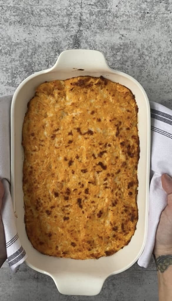 the baked buffalo chicken dip mixture in the white casserole dish, browned cheesy top.