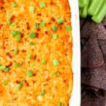buffalo chicken dip in a white casserole dish with blue corn tortilla chips and celery.