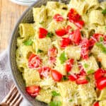 overhead shot of creamy pesto pasta in a grey bowl with diced tomatoes on top on a wood surface