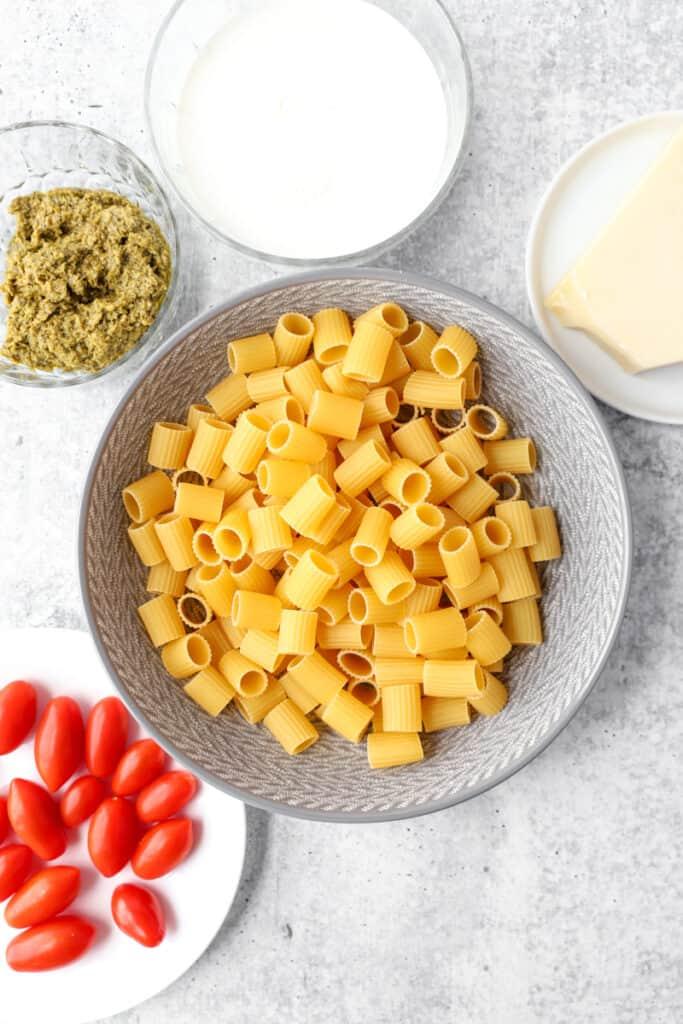 overhead shot of the ingredients: mezzi rigatoni, cherry tomatoes, Parmesan cheese, pesto, cream.
