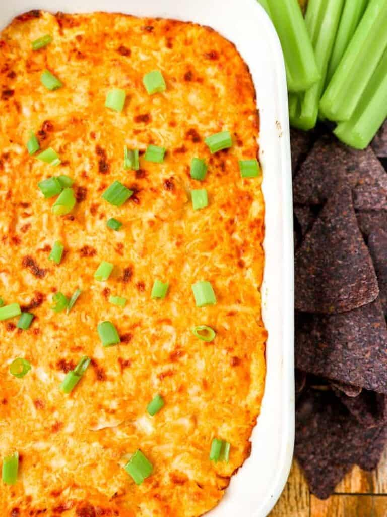 buffalo chicken dip in a white dish with blue corn tortilla chips and celery