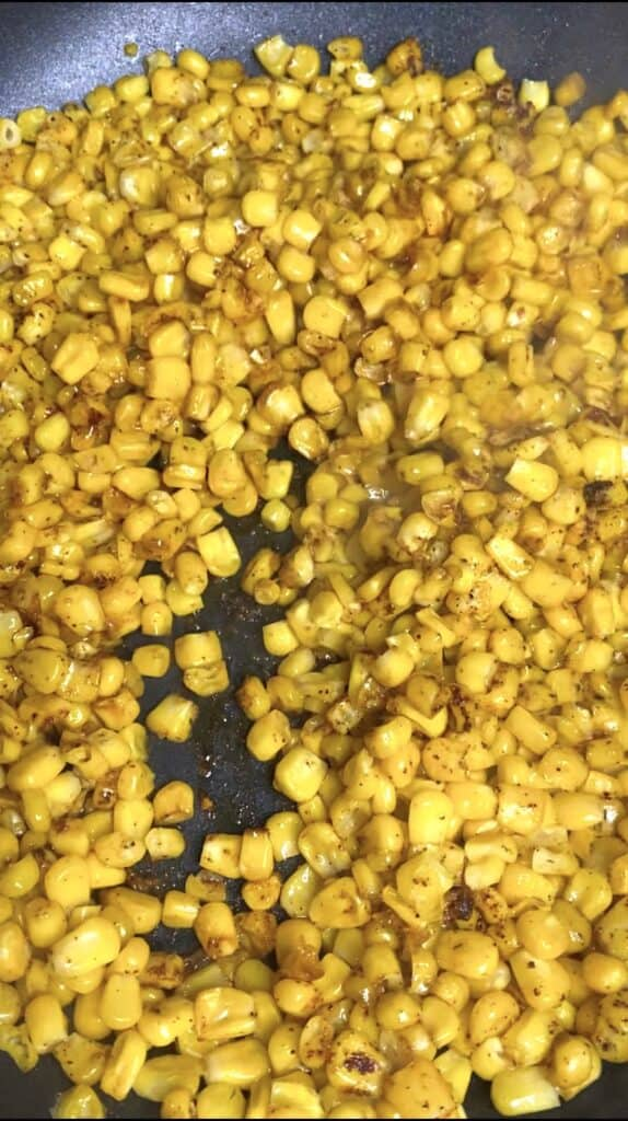 showing the seasoned corn being cooked in the pan.