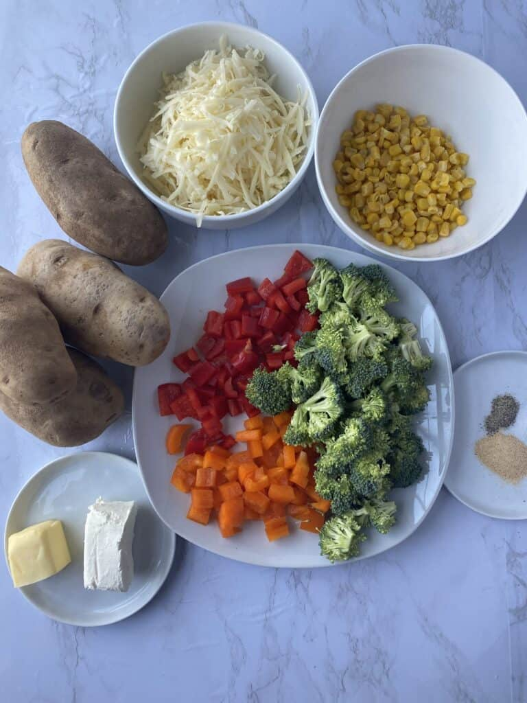 overhead shot of ingredients on a white marble surface. 4 Idaho potatoes, butter, cream cheese, bell peppers, broccoli, white Cheddar, corn, garlic powder, salt and papper.