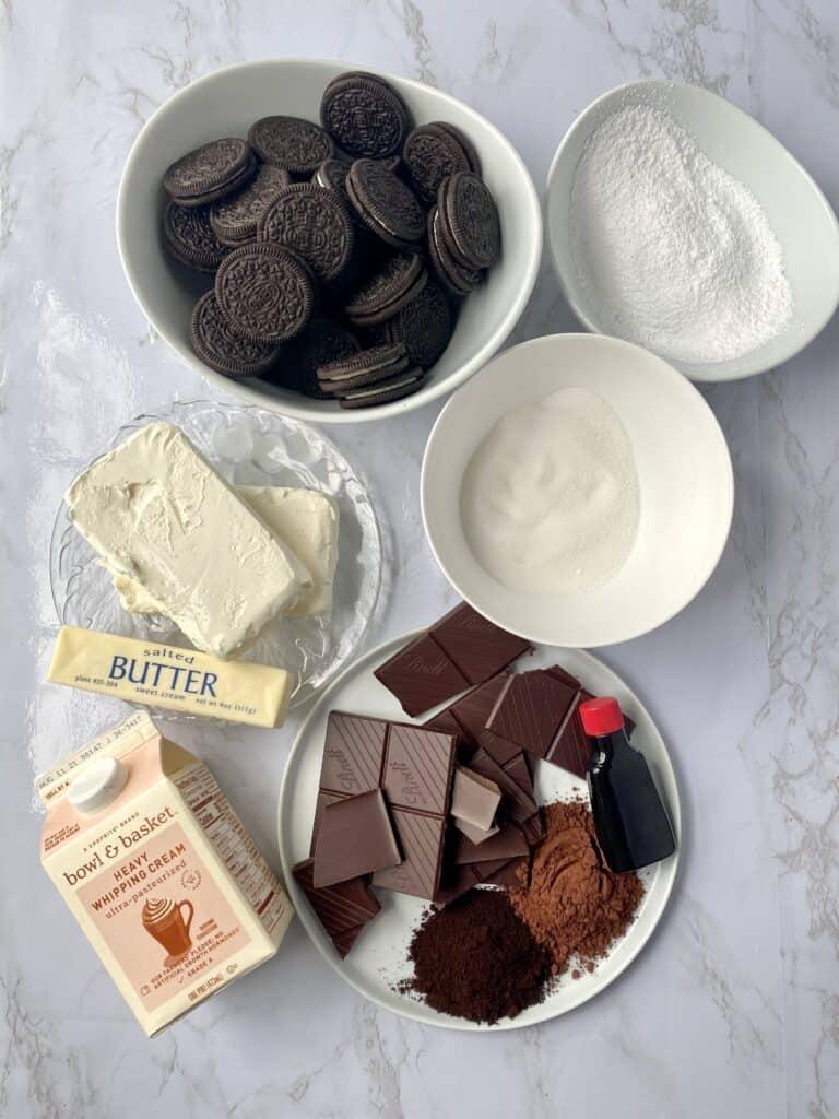 overhead shot of the ingredients: Oreos, powdered sugar, sugar, cream cheese, butter, heavy cream, vanilla extract, dark chocolate, cocoa powder, espresso powder.