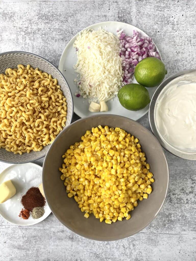 overhead shot of the ingredients: noodles, Cotija, limes, corn, crema and sour cream, garlic, red onions, butter, salt, pepper, chili powder, cayenne pepper, garlic powder.