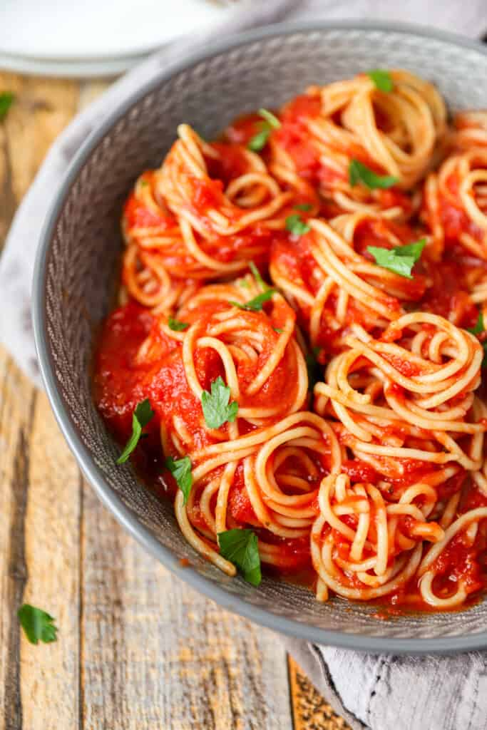 close shot of the spaghetti covered in the sauce in pasta spirals in a grey bowl on a wood pattern surface.