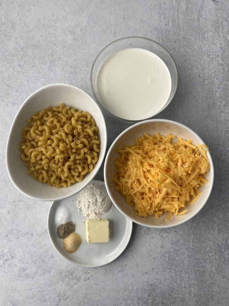 overhead shot of the ingredients: macaroni, cream, shredded Cheddar cheese, butter, flour, salt, pepper, garlic powder.