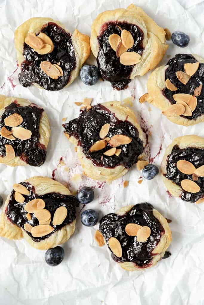 overhead shot of several of the blueberry Danishes on parchment paper with blueberries scattered about.