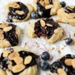 mini blueberry almond danishes on parchment paper.