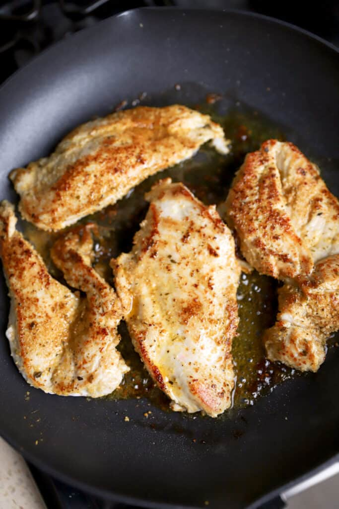 4  Cajun seasoned chicken breasts cooking in a black pan.