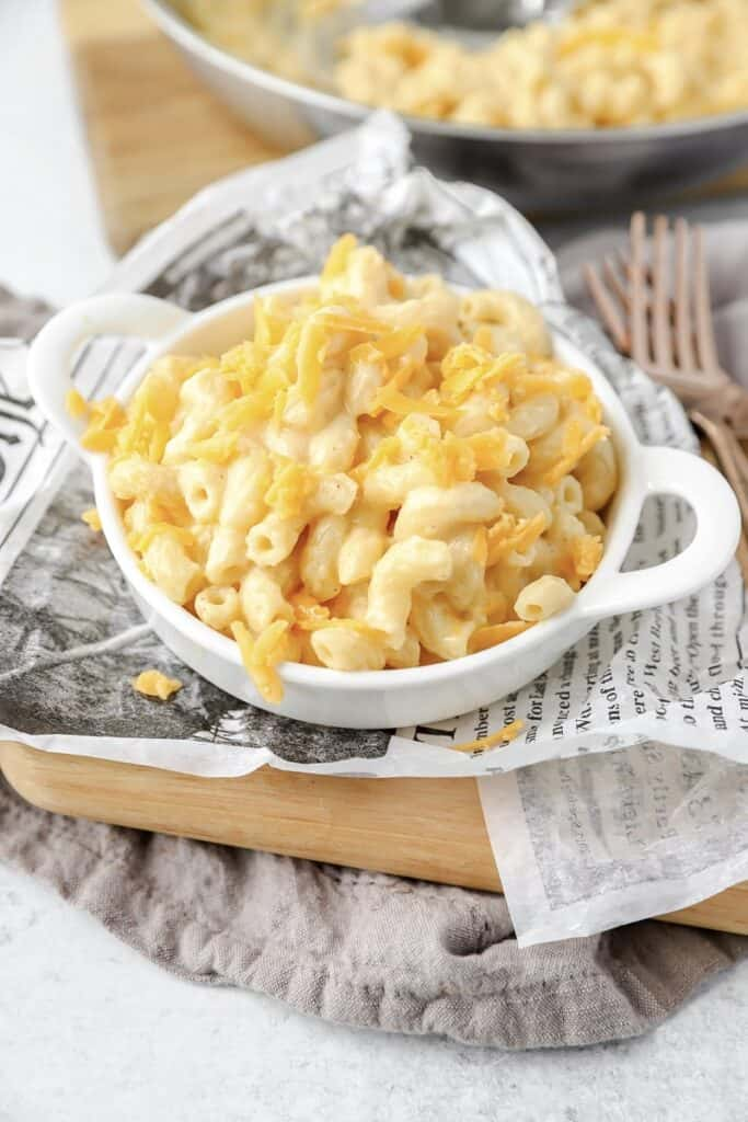 stovetop mac and cheese in a white dish on newsprint paper.